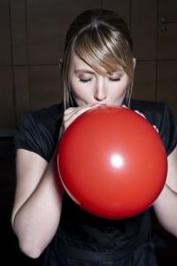 frau bläst einen roten luftballon auf
