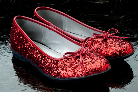 Horizontal Image Of Sequined Red Slippers On Dark Tile.